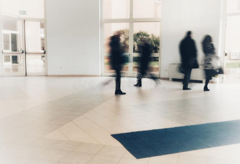 Abstract crowd of anonymous blurred people walking in shopping mall royalty free stock photography