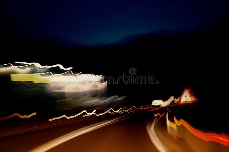 Abstract dangerous blurred driving. Abstract danger night driving, red, yellow and orange lights acceleration speed motion blur. Motion blur visualizies the royalty free stock photos