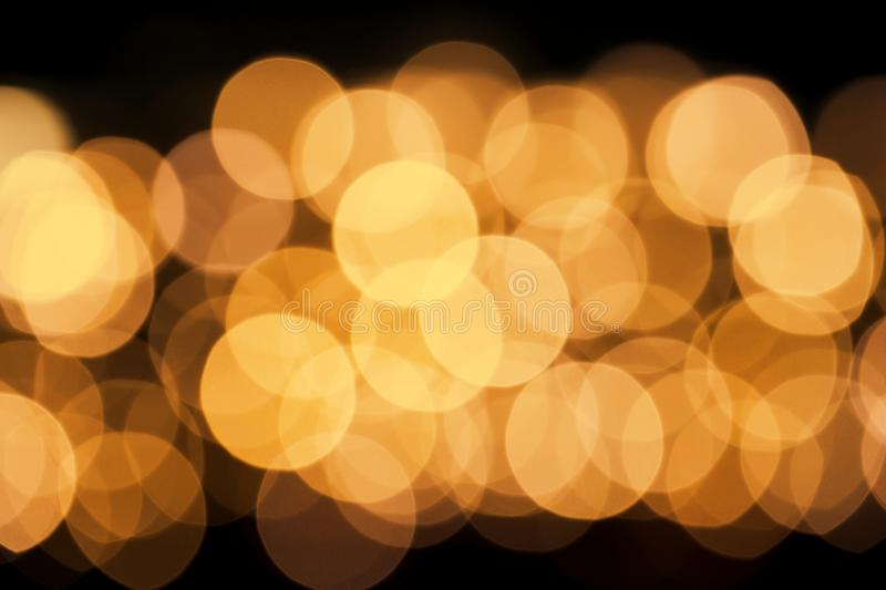 Abstract defocused glittering background. Blurry bokeh of golden lights. Christmas and holiday concept royalty free stock photos