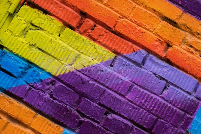Abstract detail van bakstenen muur met fragment van kleurrijke graffiti, de close-up van de straatkunst Voor achtergronden Modern stock fotografie