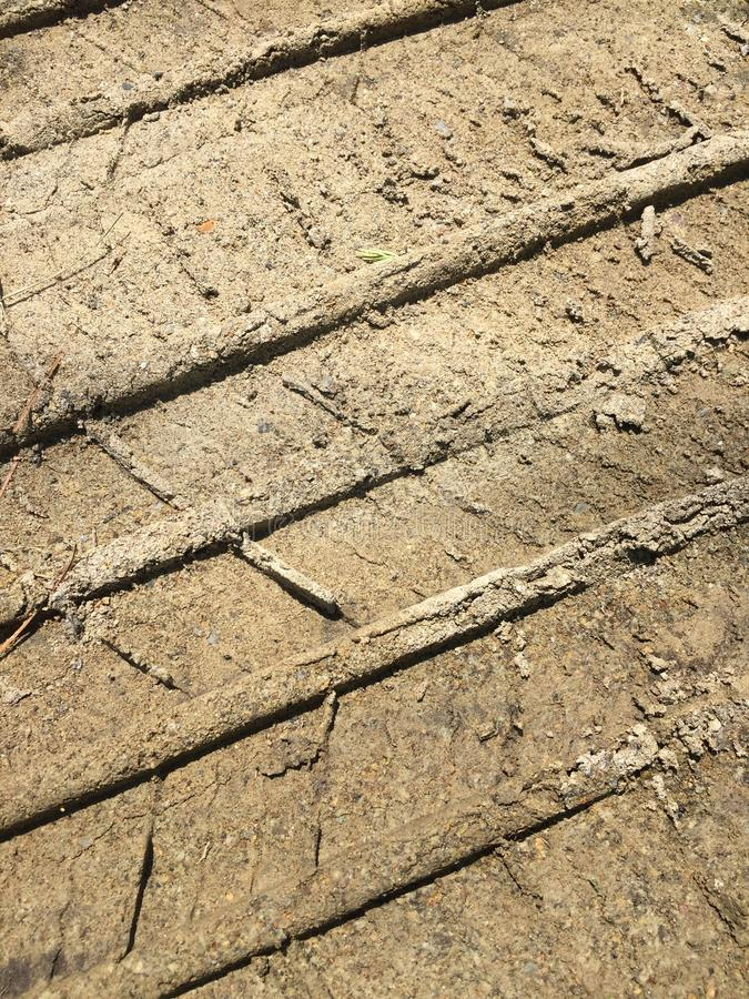 Abstract dirt tire tracks. Closeup angled vertical view of deep tire tracks on a dirt surface stock photo