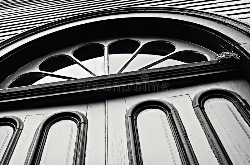 Abstract Doors Window. A monochrome abstract architectural picture of old church doors with an arched window and bird nest in the corner with siding royalty free stock images
