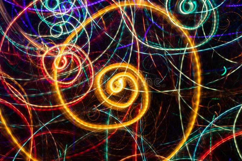 Abstract drawing of glowing multicolored spiral swirls on black background. Photographic effect with long exposure royalty free stock photos