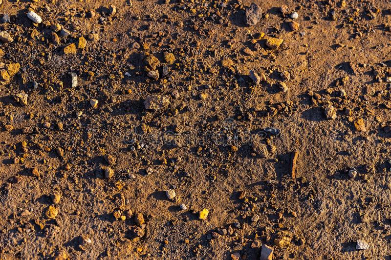 Abstract dry mud background with small rocks and selective focus stock image