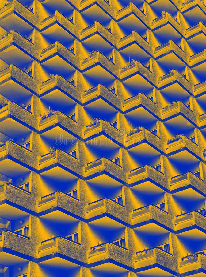 Abstract duotone yellow and blue image of large residential highrise building with geometric rows of balconies. An abstract duotone yellow and blue image of royalty free stock photography