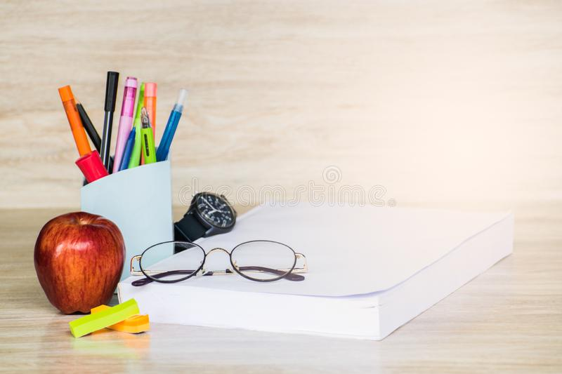 Abstract education, red apples, multicolored pens and white books with wooden backgrounds. Abstract education, apples, multicolored pens and white books with royalty free stock images