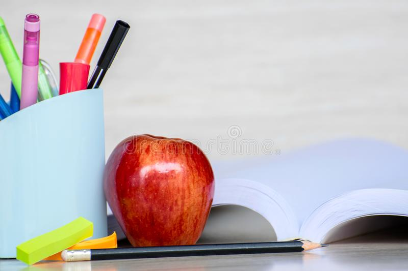 Abstract education, red apples, multicolored pens and white books with wooden backgrounds. Abstract education, red apples, multicolored pens and  books with royalty free stock images