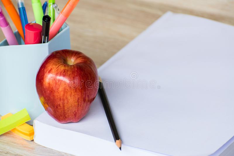 Abstract education, red apples, multicolored pens and white books with wooden backgrounds. Red apples, multicolored pens and white books with wooden backgrounds stock photo