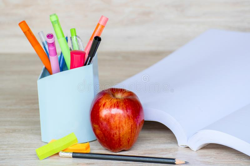 Abstract education, red apples, multicolored pens and white books with wooden backgrounds. Abstract education, red apples, multicolored pens and books with stock photos