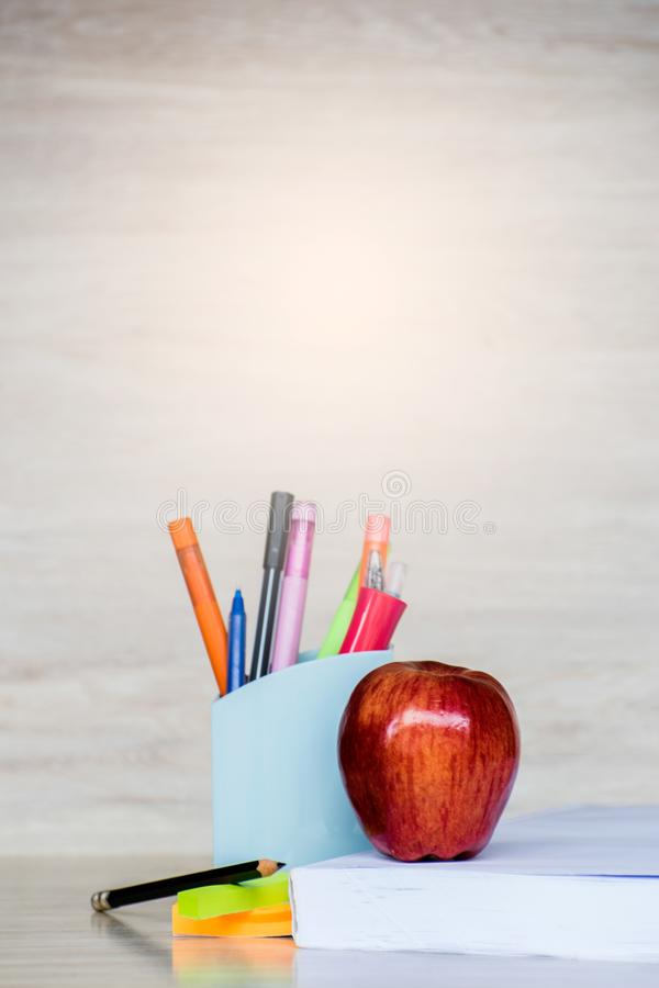 Abstract education, red apples, multicolored pens and white books with wooden backgrounds. Abstract education, red apples, multicolored pens and  books with royalty free stock image