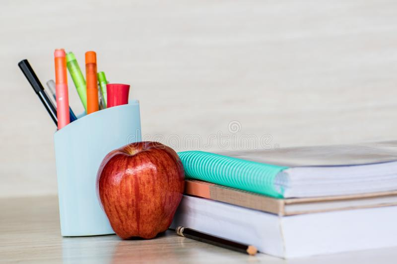 Abstract education, red apples, multicolored pens and white books with wooden backgrounds. Abstract education, red apples, multicolored pens and books with royalty free stock photos