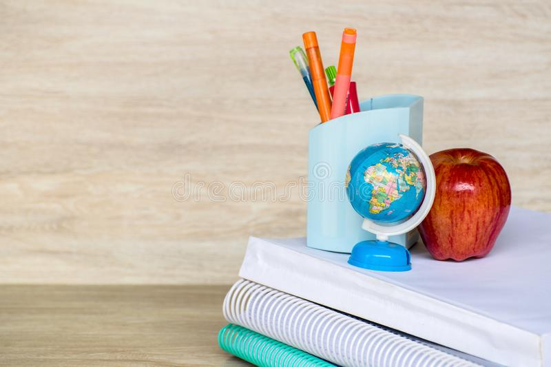 Abstract education, red apples, multicolored pens and white books with wooden backgrounds. Abstract education, red apples, multicolored pens and  books with stock photo