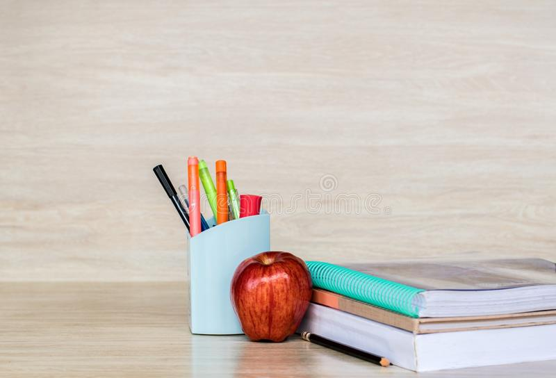 Abstract education, red apples, multicolored pens and white books with wooden backgrounds. Red apples, multicolored pens and white books with wooden backgrounds stock images