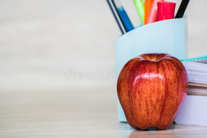 Abstract education, red apples, multicolored pens and white books with wooden backgrounds. Red apples, multicolored pens and white books with wooden backgrounds royalty free stock photo