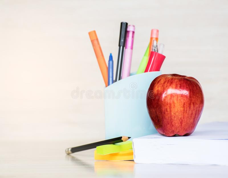 Abstract education, red apples, multicolored pens and white books with wooden backgrounds. Abstract education,apples, multicolored pens and white books with royalty free stock photography