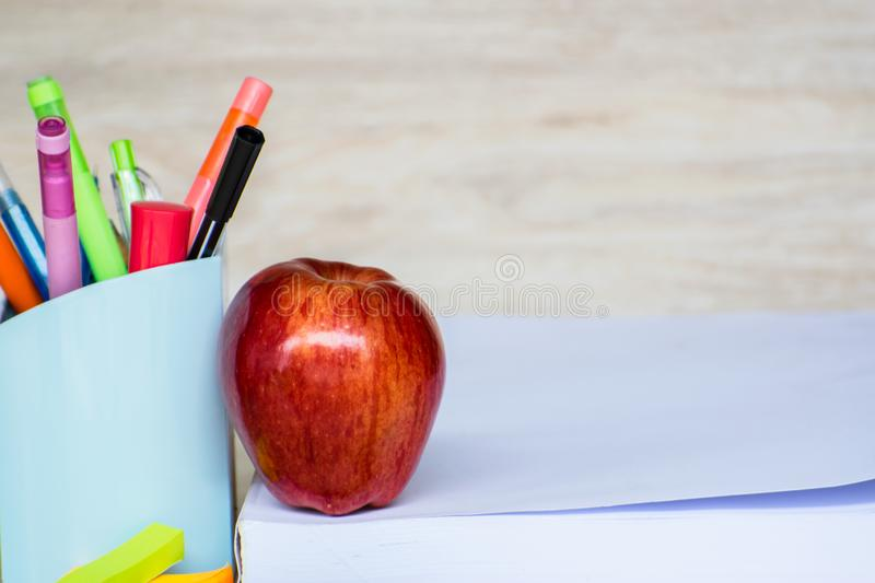 Abstract education, red apples, multicolored pens and white books with wooden backgrounds. Red apples, multicolored pens and white books with wooden backgrounds royalty free stock photos