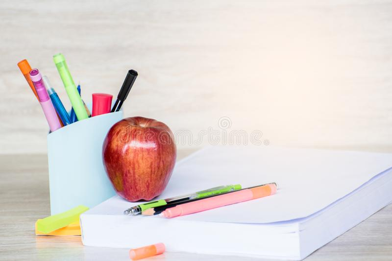 Abstract education, red apples, multicolored pens and white books with wooden backgrounds. Abstract education,apples, multicolored pens and white books with royalty free stock photo