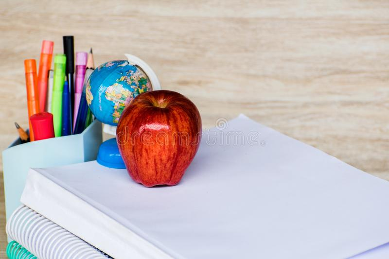 Abstract education, red apples, multicolored pens and white books with wooden backgrounds. Red apples, multicolored pens and white books with wooden backgrounds stock photography