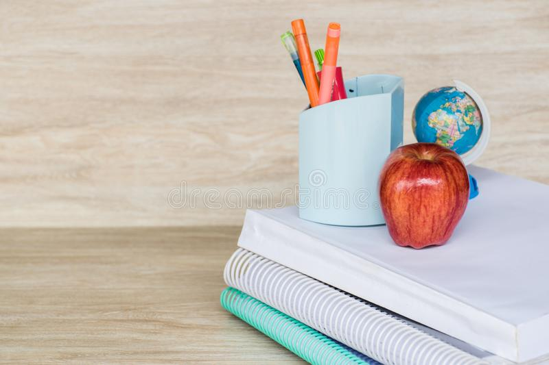 Abstract education, red apples, multicolored pens and white books with wooden backgrounds. Abstract education, red apples, pens and white books with wooden stock photography