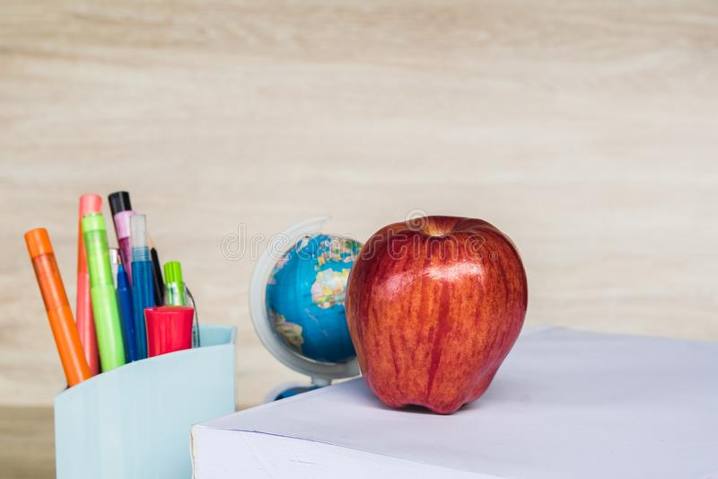 Abstract education, red apples, multicolored pens and white books with wooden backgrounds. Abstract education, apples, multicolored pens and white books with stock photo