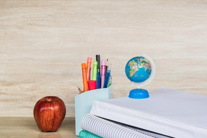 Abstract education, red apples, multicolored pens and white books with wooden backgrounds. Abstract education, apples, multicolored pens and white books with royalty free stock photos
