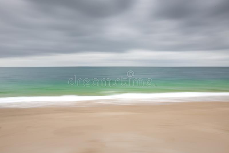 Abstract Emerald Ocean Blur. An abstract background image of a sandy beach with white waves flowing from an emerald green ocean and cloudy sky above with a royalty free stock image