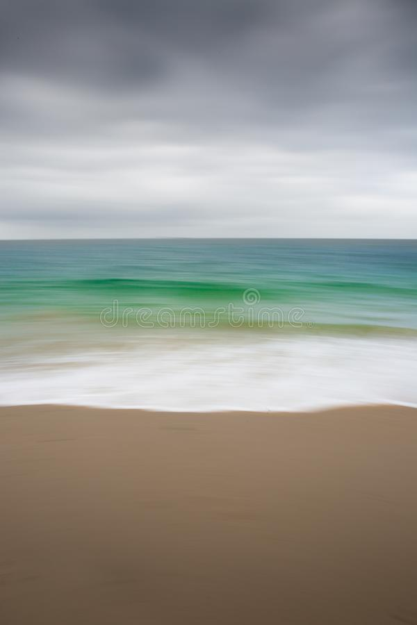 Abstract Emerald Ocean Blur. An abstract background image of a sandy beach with white waves flowing from an emerald green ocean and cloudy sky above with a stock images