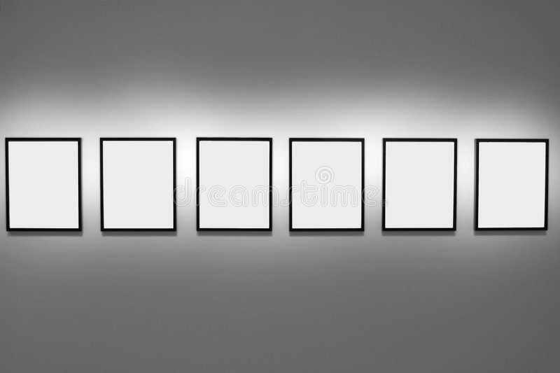 Abstract of empty picture frames. Symmetrical series of six empty picture frames hanging on a gallery wall royalty free stock image