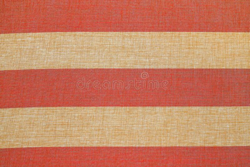 Abstract empty red and beige striped background, fabric texture, yellow and crimson knitted cloth , cotton, wool. Grunge rough royalty free stock photo
