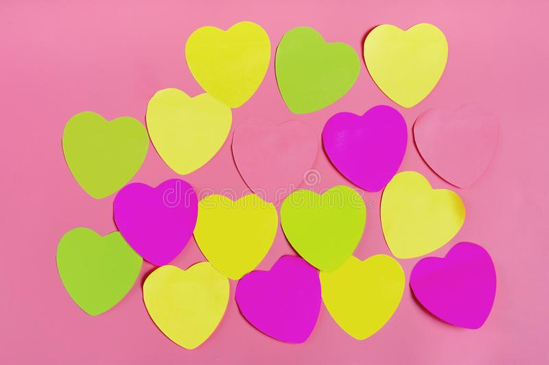 Abstract empty sticky note in the shape of a heart magnet on pink board. Valentine greeting card message.Happy Valentine`s day concept. Flat lay. Top view royalty free stock image