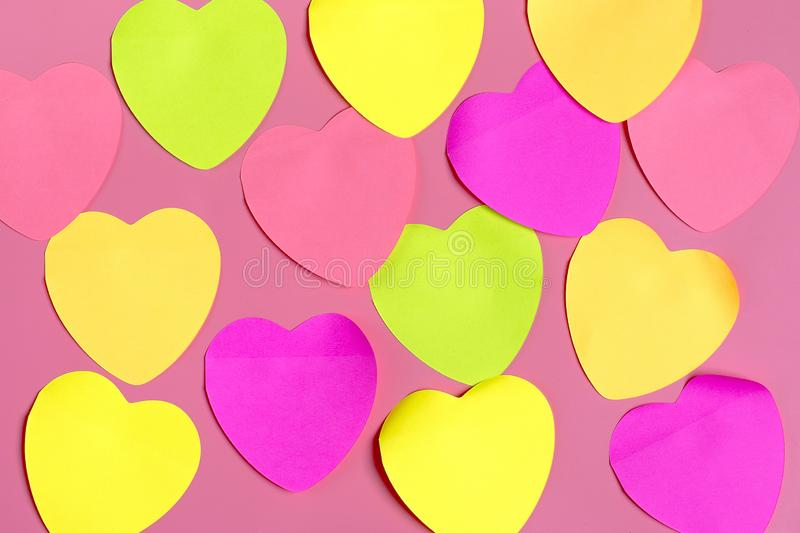 Abstract empty sticky note in the shape of a heart magnet on pink board. Valentine greeting card message.Happy Valentine`s day concept. Flat lay. Top view stock photography