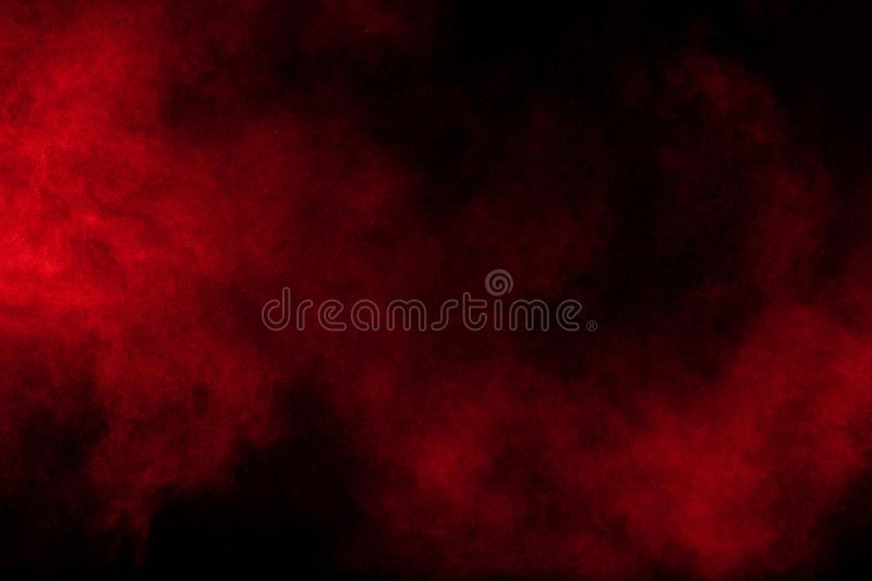 Abstract explosion of red powder on black background. Freeze motion of red powder splash stock image