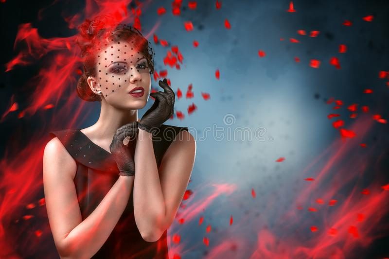 Abstract fashion portrait of young woman with flame. And smoke over dark background royalty free stock photos
