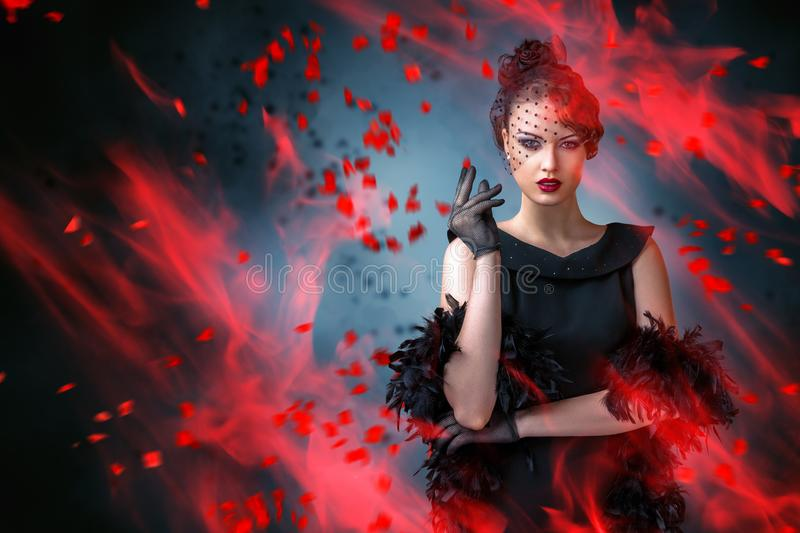 Abstract fashion portrait of young woman with flame. And smoke over dark background stock photos