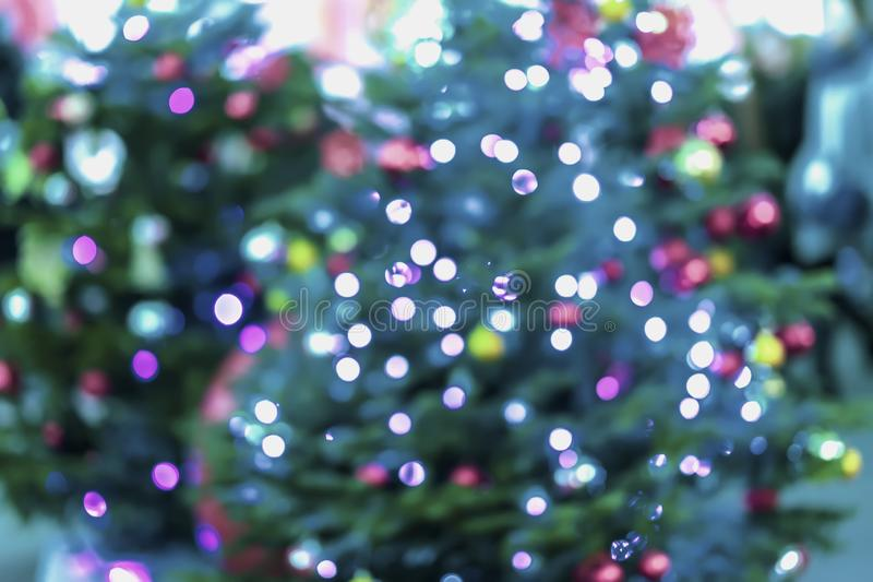 Abstract festive background of christmas fir tree, spruce with silver bokeh, unfocused sparkles of garland, decor lights royalty free stock images