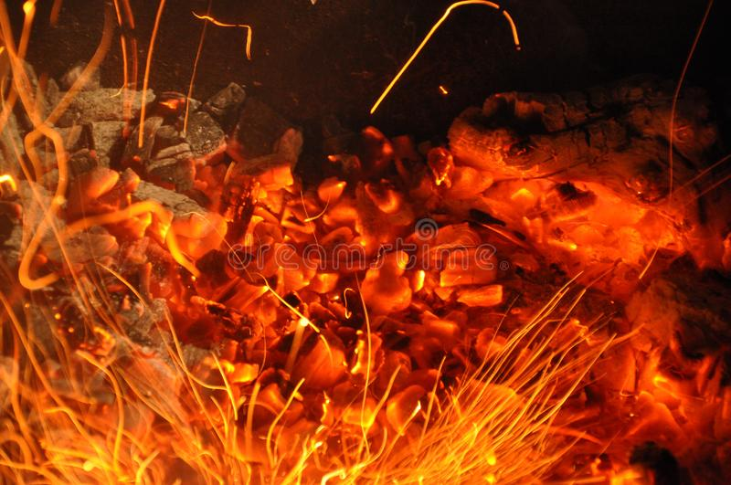 Trails of flame sparks. Burning traces glowing over black backdrop. Abstract fiery background. Orange color fire sparks closeup royalty free stock photo