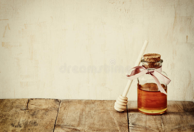 Abstract filtered image of honey glass jar. rosh hashanah (jewesh holiday) concept. traditional holiday symbols. royalty free stock images