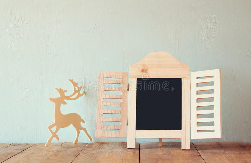 Abstract filtered photo of decorative chalkboard frame and wooden deer over wooden table. ready for text or mockup royalty free stock photography
