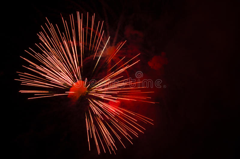 Abstract Fireworks: Red Bow-Tie in the Night. Fireworks with diverging red and white lines coming from a red puff of smoke in the black night sky resemble an royalty free stock photos