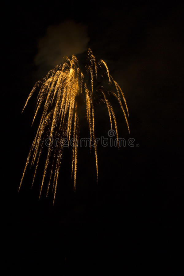 Abstract Fireworks: Shimmering Golden Rain Falling in the Night. From a faint puff of smoke come golden, shimmering, firecracker lights that appear to be falling royalty free stock photo