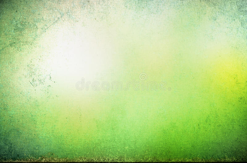 Abstract Forest Glade. Abstract grungy bordered background texture with appearance of glowing yellow sunlight in a misty green forest glade royalty free stock photo