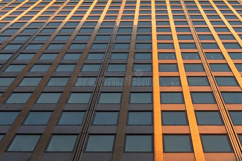 Abstract fragment of contemporary architecture. Low angle perspective view of mordern office building`s exterior with glass window. S in row royalty free stock images
