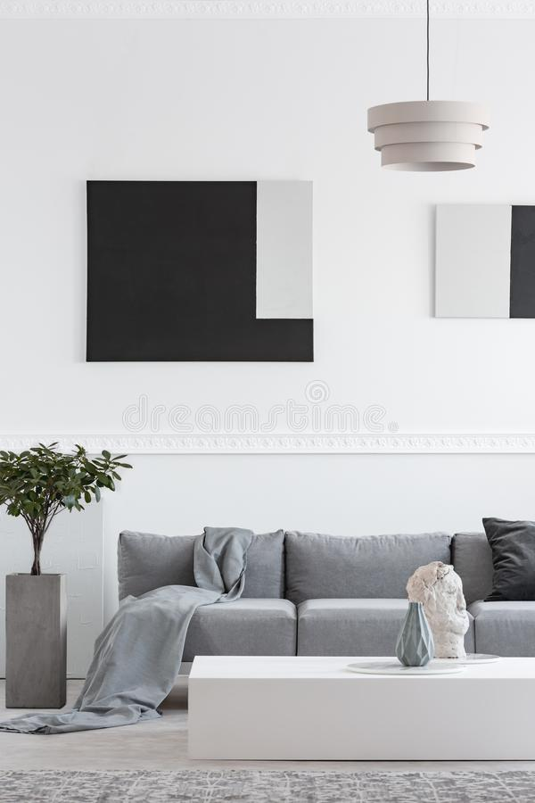 Abstract geometric black and paintings on white wall of trendy living room interior. Abstract geometric black and grey paintings on white wall of trendy living royalty free stock photos