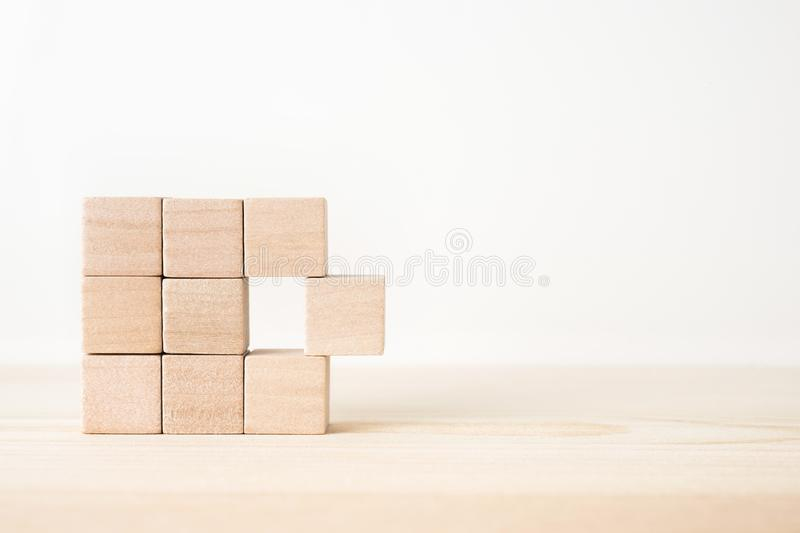 Abstract geometric real wooden cube with surreal layout on white floor background and it`s not 3D render. It`s the symbol of lea. Business and design concept stock photography