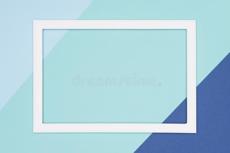 Abstract geometrical flat lay pastel blue and turquoise colored paper background. Minimalism template with empty picture frame. Abstract geometrical flat lay stock image
