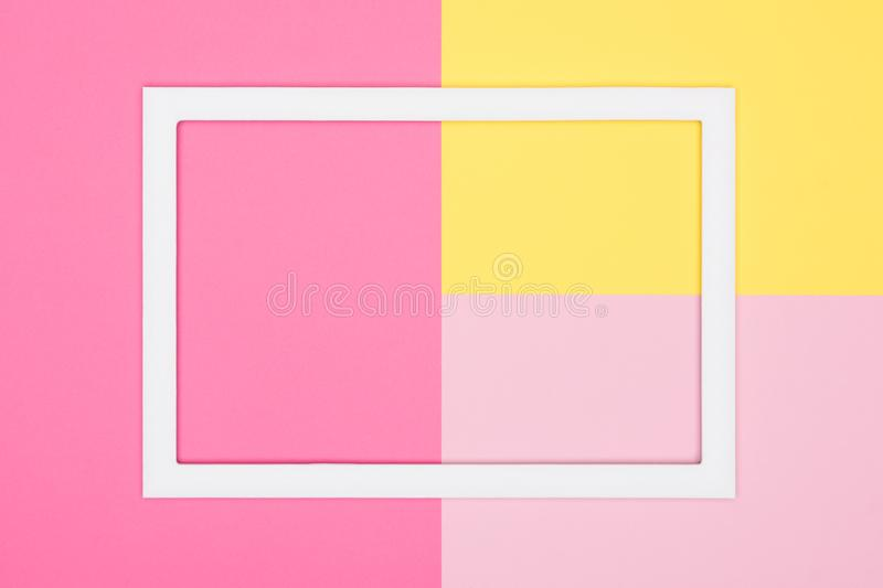 Abstract geometrical pastel pink and yellow paper flat lay background. Minimalism, geometry and symmetry template with empty frame. Abstract geometrical pastel royalty free stock photo