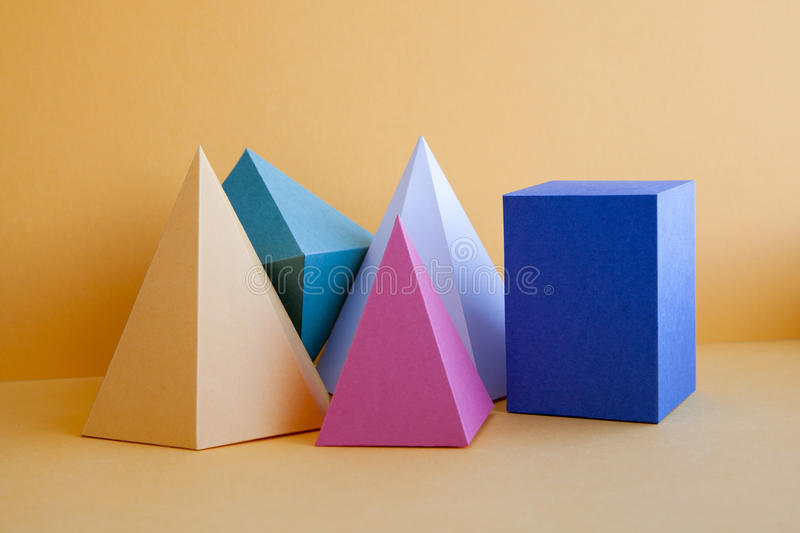 Abstract geometrical still life background. Three-dimensional prism pyramid rectangular cube on yellow background stock images
