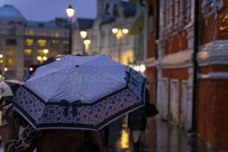 Abstract girl under the umbrella, cold rainy weather, blurred image. Seasons, weather, modern women in the city concept stock photos