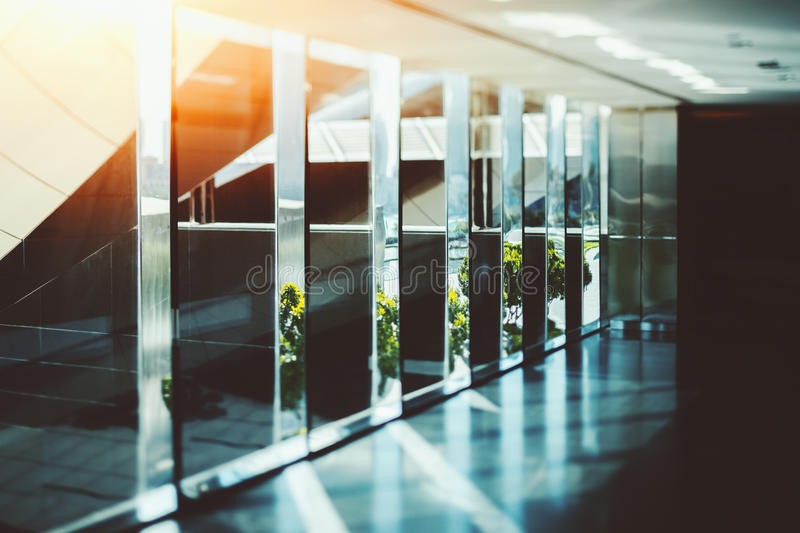 Abstract glass and chrome office interior background with sun ra. Abstract dark office interior background, the sun rays, glass, chrome columns and windows stock photo