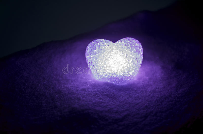 abstract glass heart on snow at night. Card for a Valentine's day. violet heart llight on black background stock photo